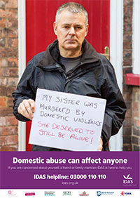 Man holding up a sign which reads - My sister was murdered by domestic violence, she deserves to still be alive!