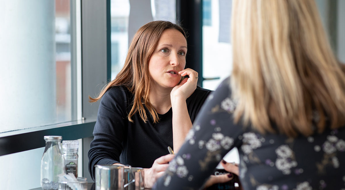 Woman talking to a support worker in a cafe